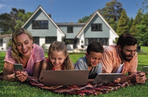 whole family outside on laying on a lawn using digital devices